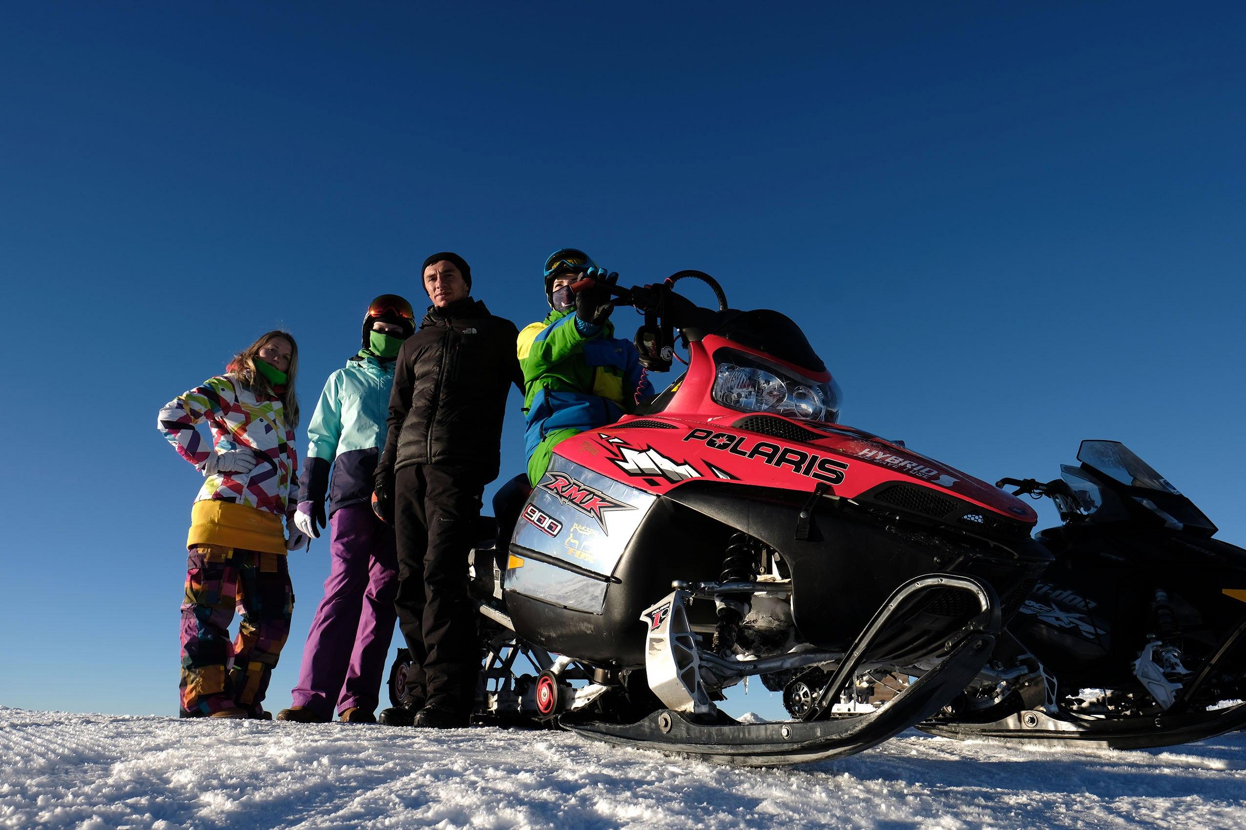 группа лыжников и снегоход